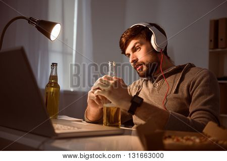 Time to have a rest. Calm young bearded guy looking attentively at the screen while sitting at the table and using a headset and drinking a beverage