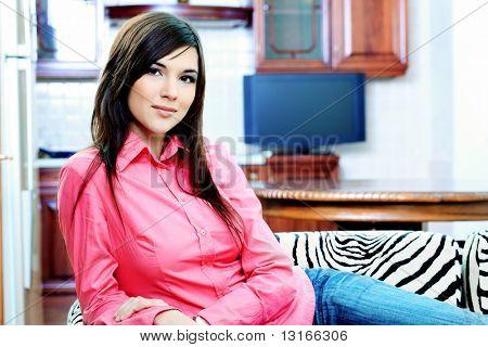 Retrato de una mujer joven feliz sentado en un sofá en casa.