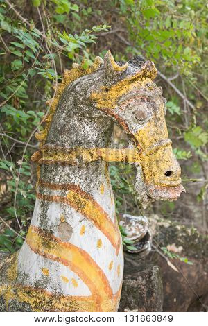 Chettinad India - October 16 2013: Ayyanar village protector Horse shrine of Namunasamudran. Old clay horse head with yellow gear and blackened by mold.