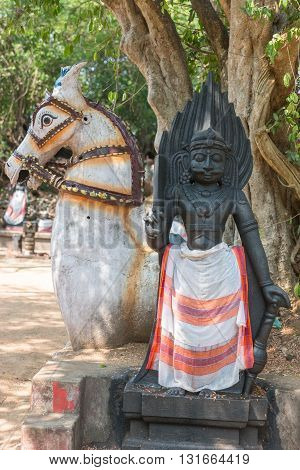 Chettinad India - October 16 2013: Ayyanar village protector Horse shrine of Namunasamudran. Ayyanar statue at altar with horse at his back.