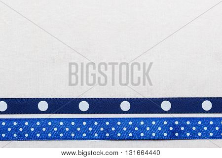 Festive celebration party frame. Polka dot navy blue satin ribbon on white cloth background