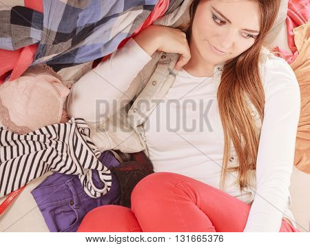 Woman Lying On Clothes. Mess And Disorder.