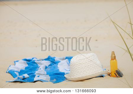 Beach set summer hat sunglasses and skin lotion lying on the sand. Vacation resting and relax