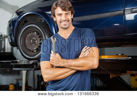 Happy Mechanic Standing Arms Crossed At Repair Shop