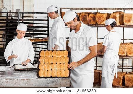 Man Analyzing Breads While Colleagues Working In Bakery