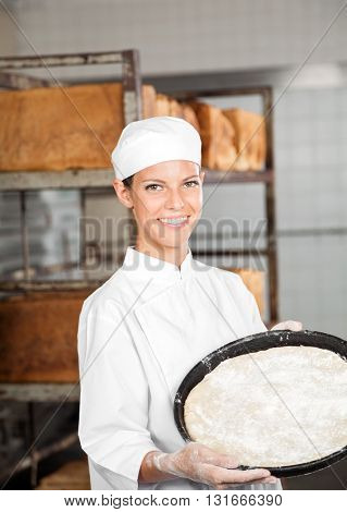 Confident Female Baker Holding Dough Tray At Bakery