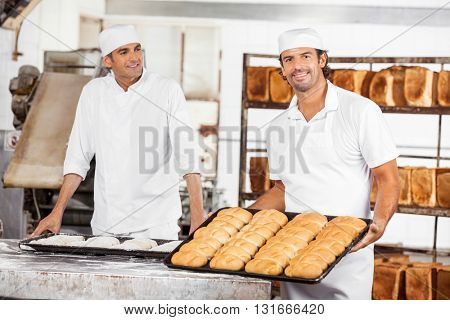 Smiling Baker Showing Breads In Baking Tray By Colleague