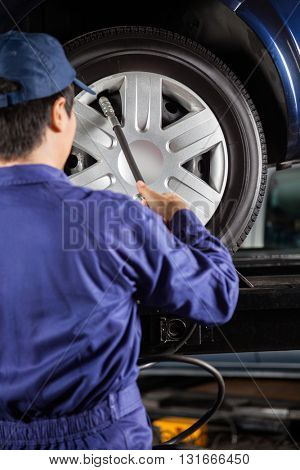 Technician Filling Air Into Car Tire At Garage
