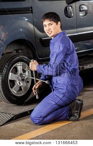 Confident Mechanic Fixing Car Tire At Garage