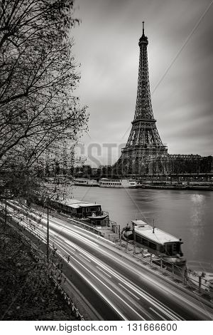 The Eiffel Tower and Seine River in early morning with clouds and car light trails in Black & White. Paris, France