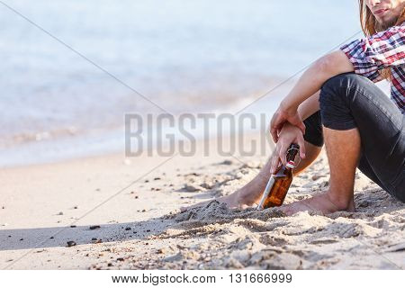 Man Depressed With Wine Bottle Sitting On Beach Outdoor