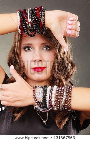 Pretty young woman wearing multiple bracelets jewellery necklace in black elegant evening dress on gray