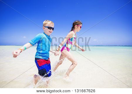 Children splashing in the ocean on a tropical beach vacation. Smiling and holding hands while splashing in the water on an idyllic beach