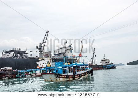 Image of Nha Trang Bay harbor in Vietnam. Nha Trang is a coastal city in the south central coast and is popular for its scenic bay beauty. Ships and fishing boats are seen at the harbor.