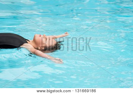 Young girl floating with closed eyes in swimming pool. Smiling child relaxing in swimming pool. Relaxing girl in swimming pool.