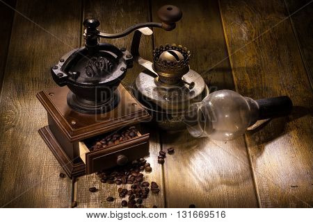 Coffee mill and old oil lamp on a wooden table