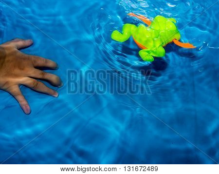 Boys swimming pool blue with green frog toy.