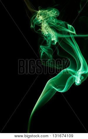Abstract art. Color emerald smoke from the aromatic sticks on a black background. Background for Halloween. Texture fog. Design element. The concept of aromatherapy.