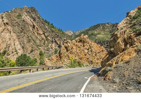 Two-lane winding road through the Wasatch Mountains in Utah with just a hint of fall here and there.