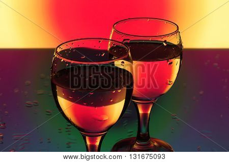 a glass of water on a red and yellow background with a beautiful romantic light and drops