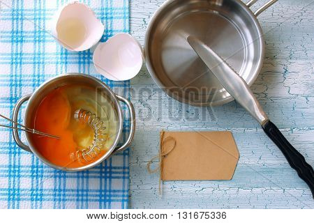 broken raw egg in pan whisk for whipping griddle knife and paper label on wooden table