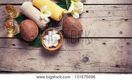Coconuts coconut oil and towels on vintage wooden background. Spa setting. Selective focus. Natural organic spa products. Place for text. Flat lay. Toned image.