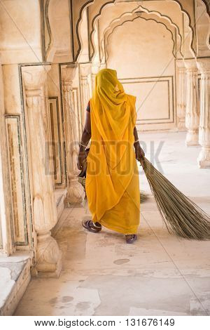 A local female sweeper walking with broomsticks through the corridors of the beautiful Amber fort in Jaipur, Rajasthan. She is seen wearing a yellow saree and holding broomsticks.
