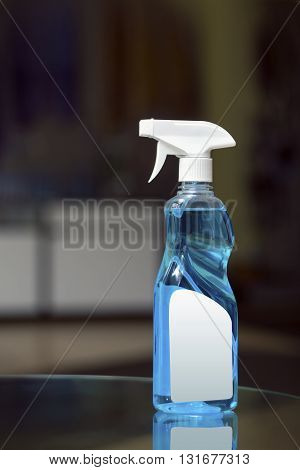 Plastic transparent sprayer with blue liquid and white elements. blank label in a blurred background