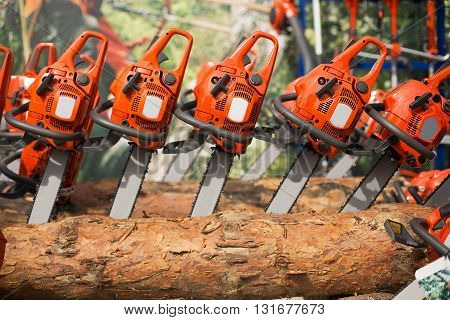 New electric chainsaw machines on firewood, depth of field shot