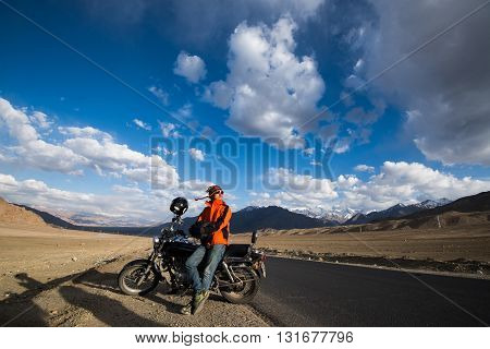 A young man with the motorbike on the road in Ladakh, India.