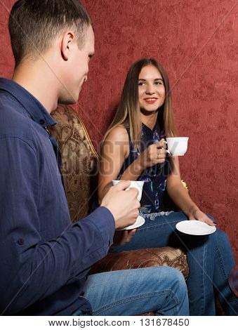 family relationships, a young couple sitting on a sofa and drink tea, they are smiling and happy.