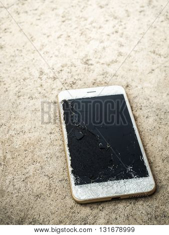 Close up of broken mobile phone drop on cement floor with copy space High Contrast Shallow Depth of Field