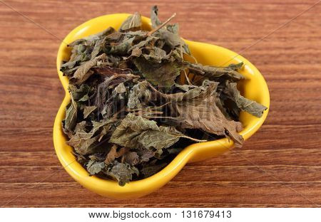 Heap of healthy dried lemon balm in yellow bowl on wooden table sedative herbs concept for healthy nutrition and herbalism