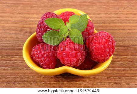 Fresh raspberries and leaf of lemon balm in yellow bowl on wooden table concept of healthy food and dessert
