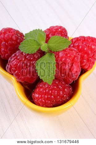 Fresh raspberries and leaf of lemon balm in yellow bowl on white wooden table concept of healthy food and dessert