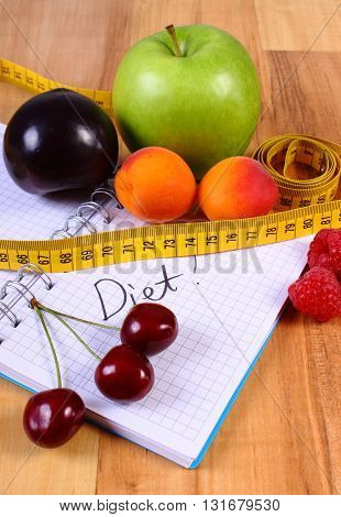 Fresh fruits and tape measure with notebook for writing notes concept of slimming diet and healthy nutrition