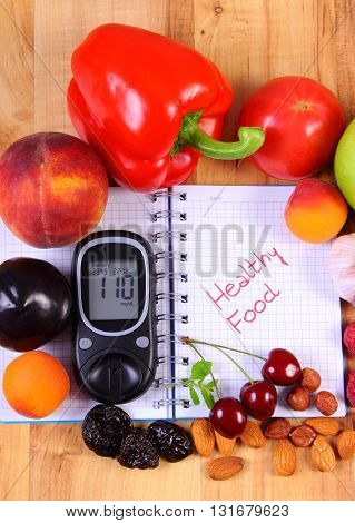 Fresh fruits vegetables and glucose meter on notebook for writing notes concept of healthy nutrition diet and diabetes sugar level