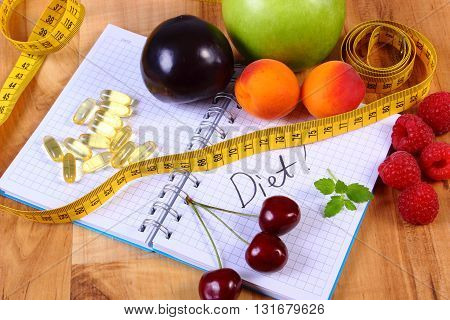 Fresh fruits tape measure and tablets supplements on notebook for writing notes choice between healthy eating and slimming pills