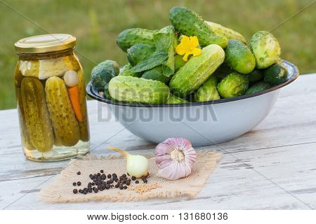 Ripe cucumbers in metal bowl spices for pickling and jar marinated cucumbers on old table in garden on sunny day