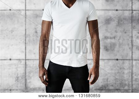 Cropped Studio Shot Of Dark Skinned Young Male Posing Against White Copy Space Wall Wearing White T-