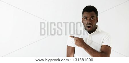 Advertising Concept. Portrait Of Young Handsome African Man Wearing Casual Clothes Looking At The Ca