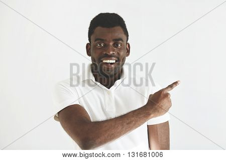 Look At That! Headshot Of Handsome Young African Man In White Polo Shirt Looking And Smiling At The