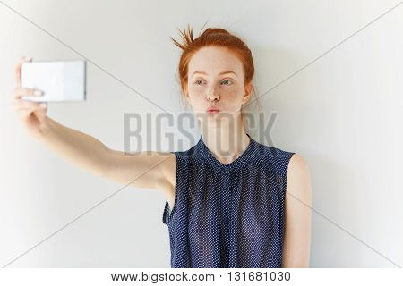 Portrait Of Beautiful Redhead Girl Wearing Spotted Dress Making Self-portrait Using Cell Phone, Send