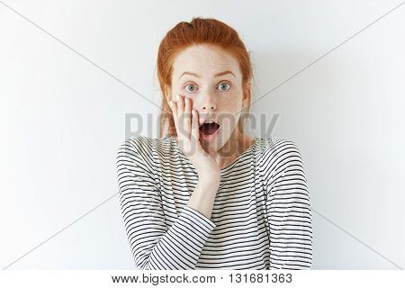 Young Redhead Woman With Surprised Expression Looking At The Camera, Screaming With Mouth Wide Open.