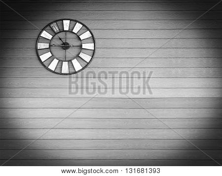 Old vintage black and white color clock on wooden plank wall background.