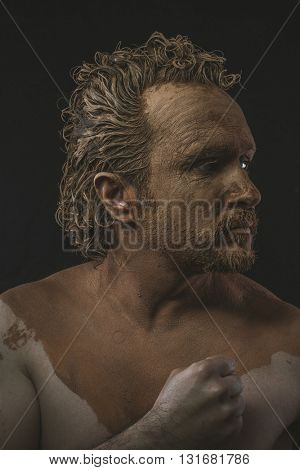 covered with mud all over her naked body on black background man. adventure and risk, competition force