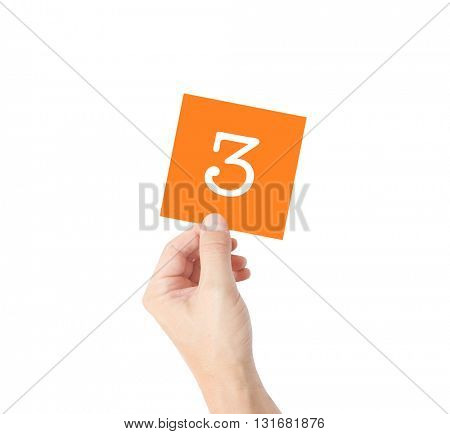 3 written on a card held by a hand