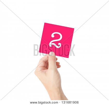 2 written on a card held by a hand