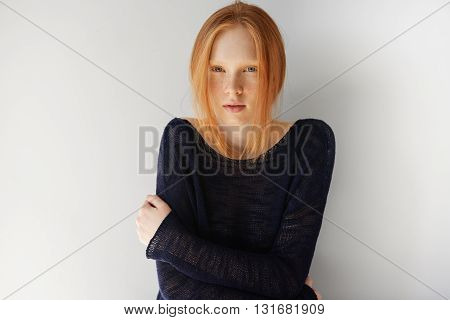 Close Up Portrait Of Sad Or Disappointed Young Woman With Red Hair Wearing Casual Top, Looking At Th