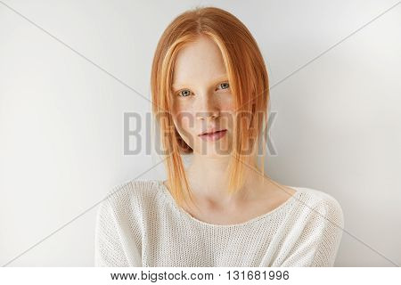 Isolated Shot Of Attractive Young Redhead Female Wearing Stylish White Top Looking At The Camera Wit